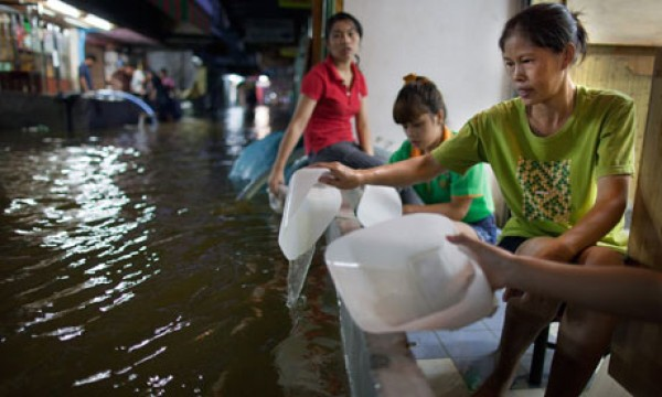Thai women use plastic containers in an attempt to bale floodwaters out of their home in Bangkok on Thursday. Photograph: Paula Bronstein/Getty Images