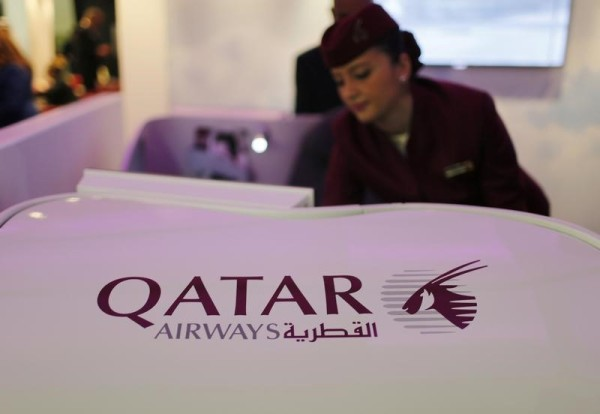 A Qatar Airways flight stewardess shows the airline's new business class seat during the Arabian Travel Market exhibition in Dubai